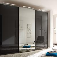 Schwarze Hochglanzflächen mit Spiegel und LED-Beleuchtung am Kleiderschrank